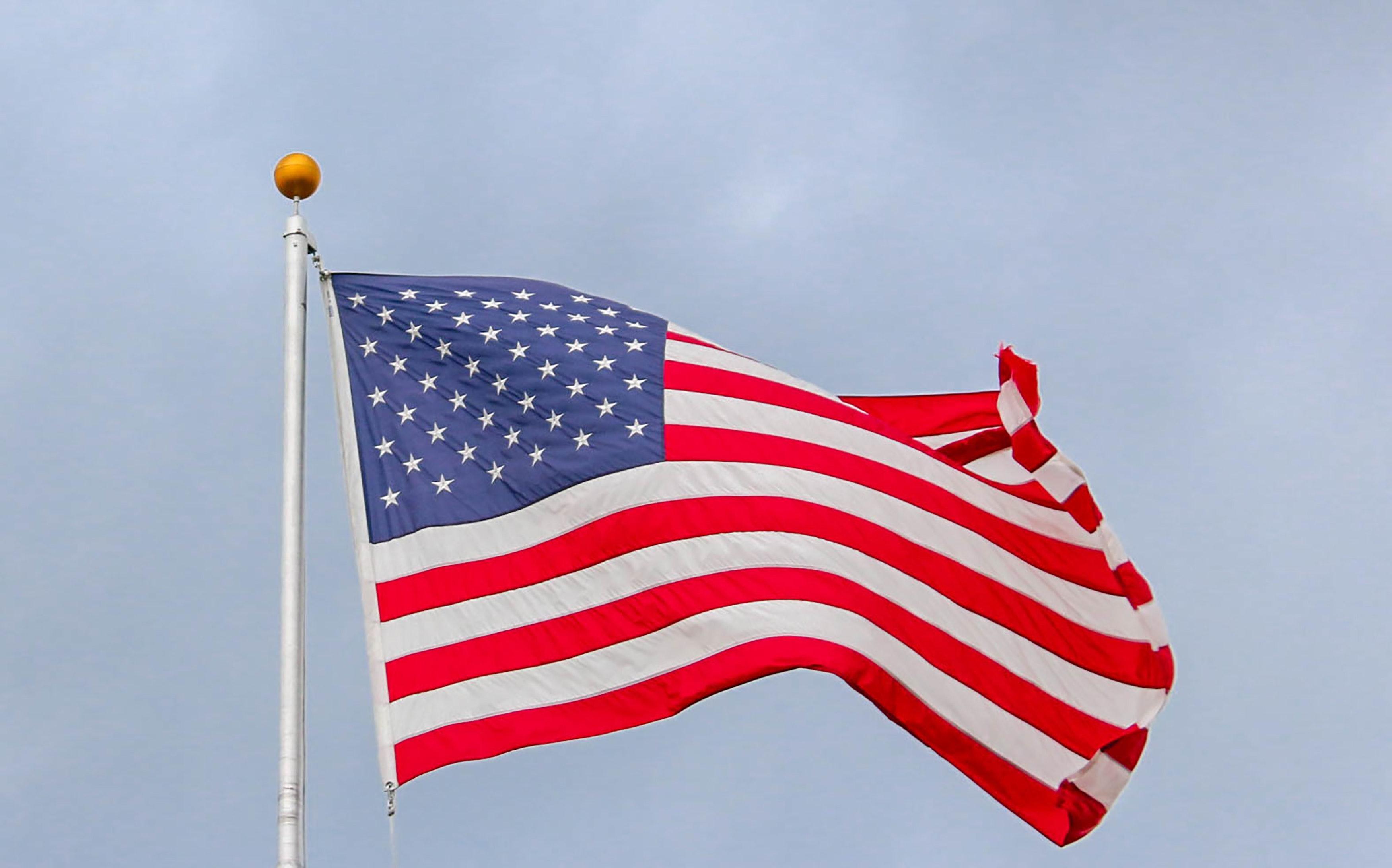usa-flag-waving-on-white-metal-pole-1550342
